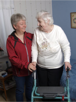 an elderly in a walker assisted by her companion