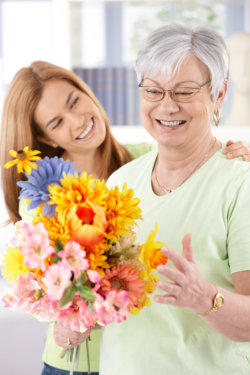 an elderly woman holding a flower with her companion